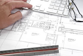 A photo of a building plan and a ruler
