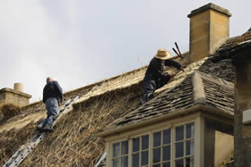 Photo of thatchers fixing a roof